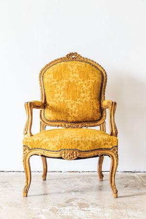 Yellow vintage armchair on white wall. Stock Photo