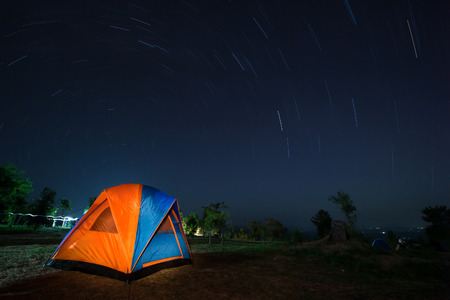 star trail: Spiral star trail with colorful tent in Thailand. Stock Photo