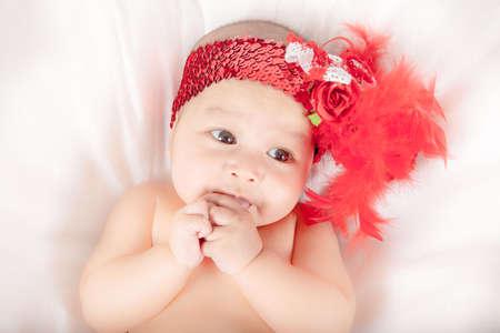 ojos negros: Peque�o beb� lindo con los ojos morados grandes y flor roja en el pelo