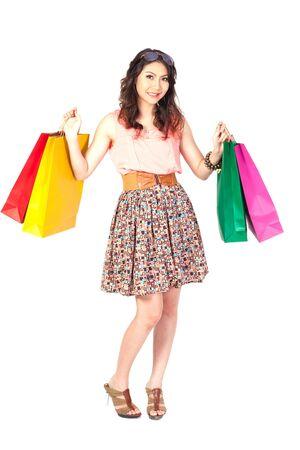 compras compulsivas: Mujer con bolsas de la compra en el fondo blanco. Foto de archivo