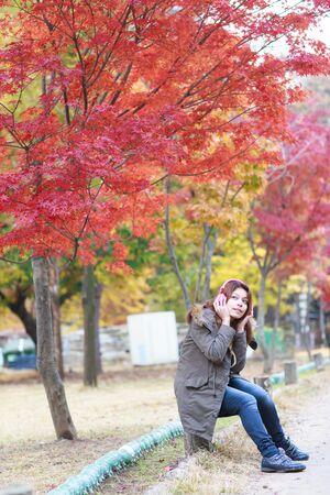 woman listening music outdoors in autumn season. photo