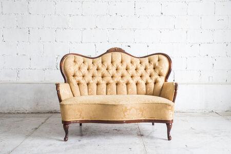 white leather: Yellow sofa armchair on white wall.