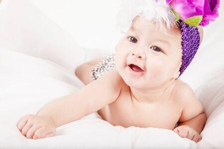 ojos negros: Peque�o beb� lindo con los ojos morados grandes y flores en el pelo