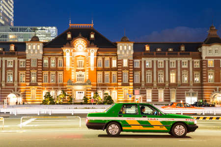 taxi famous building: TOKYO - DECEMBER 12: Pedestrians at the exterior Tokyo Station December 12, 2013 in Tokyo, JP. The station recently completed 5 years of renovations. Editorial