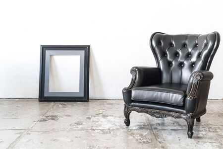Black vintage armchair and frame on white wall.