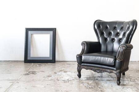 Butaca de la vendimia y marco negro en la pared blanca. Foto de archivo - 53165473