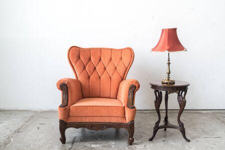 white sofa: Orange vintage sofa and lamp on white wall.