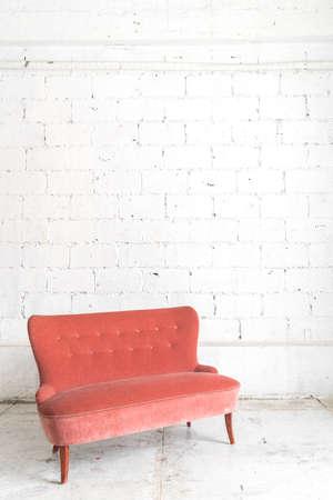 white sofa: Orange vintage sofa on white wall.