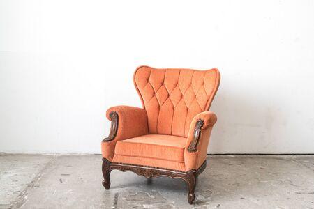 white sofa: Orange vintage sofa and on white wall. Stock Photo