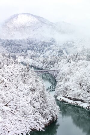 Bridge on a river with snow mountain as background in Tadami, Fukushima, Japan. Stock Photo