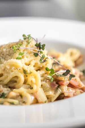 bacon and eggs: Closeup of traditional spaghetti carbonara with a bacon, eggs and cheese sauce. Stock Photo