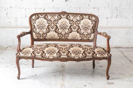 white sofa: Brown vintage sofa on white wall.