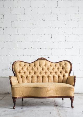 white sofa: Yellow vintage sofa on white wall.