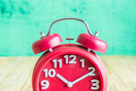 Red alarm clock on wooden old background