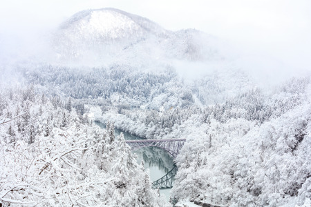 Bridge on a river with snow mountain as background in Tadami, Fukushima, Japan. Imagens