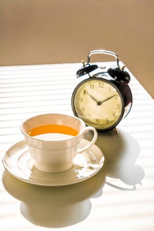 Close-up photo of clock and tea on office desk Stock Photo