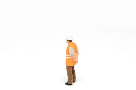 figurine: Miniature people worker wearing safety construction concept on white background with a space for text Stock Photo
