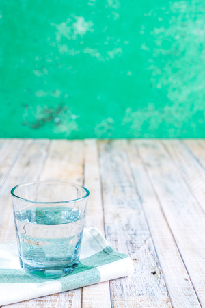 clematis: Water in a glass on a wooden background.