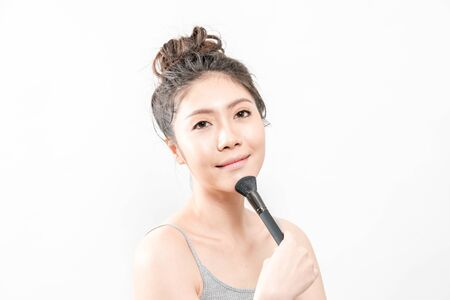 Beauty Asian Girl with Cosmetics Makeup.She applying powder brush on her face.