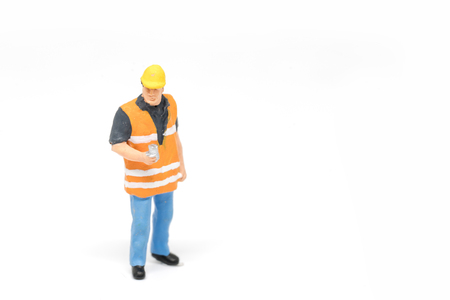 Miniature people worker wearing safety construction concept on white background with a space for text 写真素材