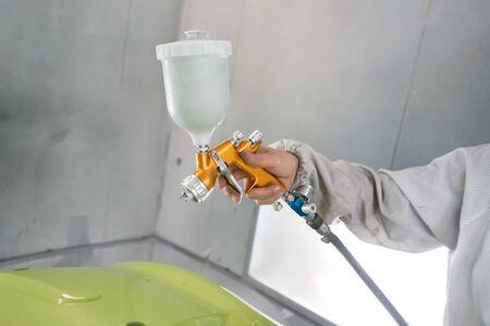 repairman painter in chamber painting automobile car bumper