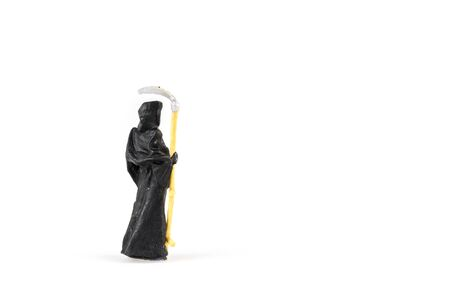 Miniature grim reaper on white background with space for text