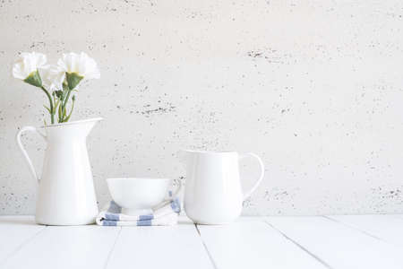 work from home: Interior with decorative vase and cup of tea on table top and white wood board, Retro home.