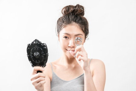 Beauty Asian Girl, She using curler to have beautiful eyelashes. Stock Photo