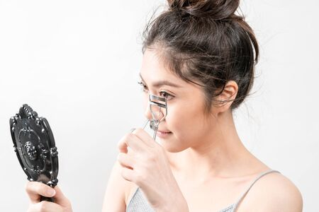 Beauty Asian Girl, She using curler to have beautiful eyelashes. 写真素材
