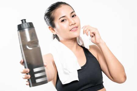 portrait of young woman wearing sport clothes and drinking water on white background.