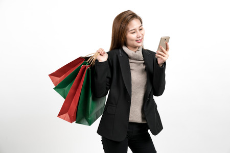 A woman holds a shopping paper bag and is happy watching a mobile phone.on white background