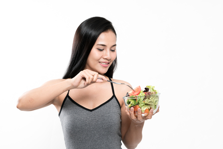 portrait of a healthy woman eating a salad indoor 写真素材