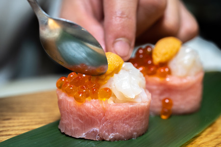 Closeup of chef hands preparing japanese food. Japanese chef making sushi at restaurant. Stock Photo