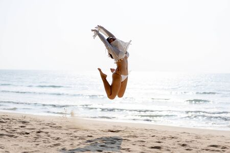 Happy young woman in bikini jumping of joy and success on the beach Reklamní fotografie - 132096496