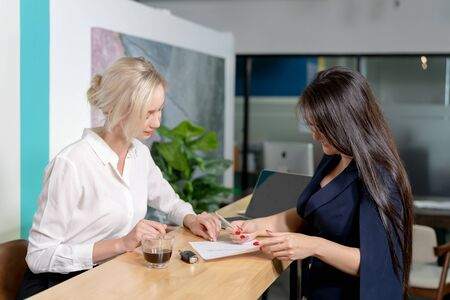 Writing signature. Two women are checking the documents and signing the contract in a job recruitment paper or insurance document. Stok Fotoğraf