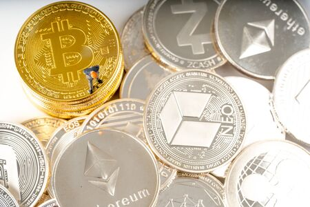 Miniature people business man standing on bitcoins coins. Cryptocurrency mining concept
