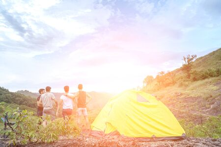 Group of Friends set up a Tent in the Mountains in the Fresh Air.They Feel very Successful and Happy from Hiking in Nature. Multiracial Young Adults Travel Hiking and Adventure in forest.
