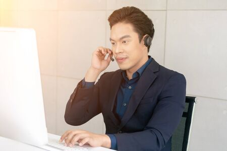 Young Male Technical Customer Support Operator Dispatcher Working with Headset in Center Office