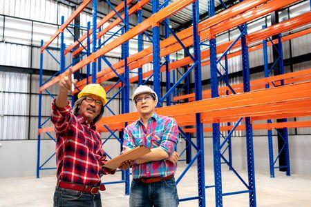 Deux ingénieurs industriels asiatiques utilisent un ordinateur tablette à écran tactile pour vérifier l'intérieur de l'entrepôt de distribution. Les employés utilisent une tablette dans l'entrepôt du centre logistique.