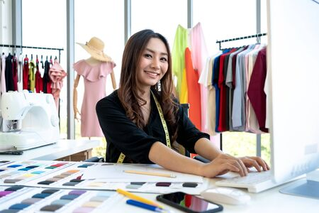 Happy smiling Asian creative fashion designer is working owner working in her tailor shop.