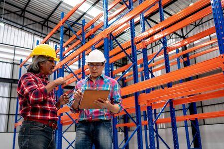 Zwei asiatische Wirtschaftsingenieure verwenden Touchscreen-Tablet-Computer, die das Innere des Distributionslagers überprüfen. Mitarbeiter verwenden Tablet-Computer im Lager des Logistikzentrums.
