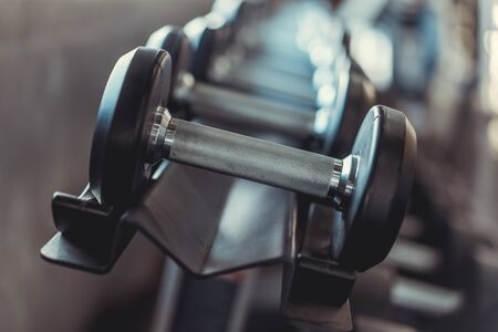 Rows of Metal Dumbbells on Rack in the Gym. Weight Training Equipment in Modern Sports Club. Stok Fotoğraf