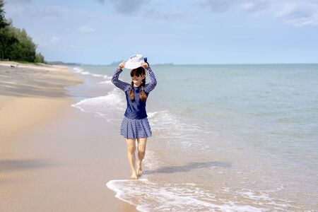 Happy middle age senior woman is Enjoying and running Summer Vacation on the beach, Thailand.