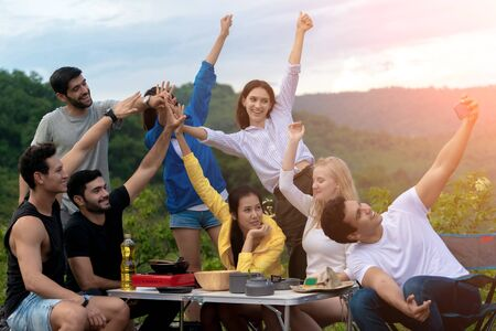 Groups of Multiculturalism Friends Relaxing are Enjoying Outside Tents Camping and Taking Selfies with Kitchen Equipment on the Table in the Forest.