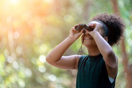 Petite fille afro-américaine avec des jumelles lors d'une randonnée en forêt. Happy Kid jouant à l'extérieur en journée d'été. Fille à l'aide de jumelles dans la jungle.