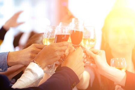 Gros plan sur des verres de champagne ou de vin. Groupe de gens d'affaires célébrant le nouvel an à la fête de bureau. Les amis ont heureusement organisé une fête et des acclamations ensemble sur le lieu de travail. Banque d'images