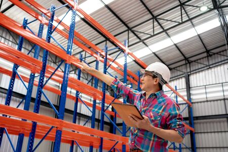 Asian Industrial Engineer Uses Touchscreen Tablet Computer Checking Interior of Distribution Warehouse. Employee use tablet computer at logistics center warehouse.