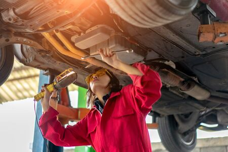 Woman Mechanic Examining Under the Car at the Repair Garage. Asian young female checking and maintenance the car. Asian young female car repair worker. Foto de archivo
