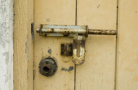 a Rusty Padlock on a yellow wooden door photo