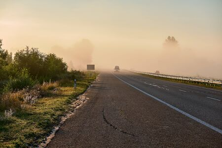 Fog on highway. Trees in haze. green bushes and wildflowers along road. Asphalt road with separate lane and bumper. Car bus on road with headlights on. Wet road. Stock Photo